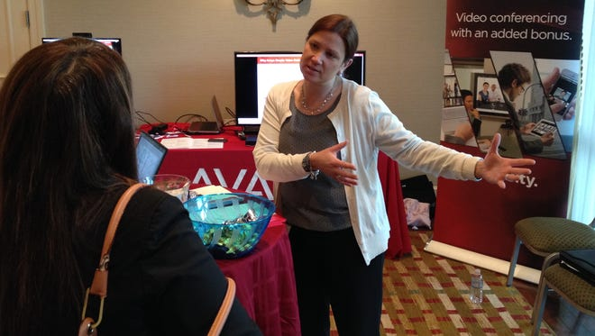 Karen Kelleher of Avaya makes a quick pitch to an attendee on May 8, 2014 at the Westchester County Association's Health Tech '14 conference in the Tarrytown DoubleTree hotel.
