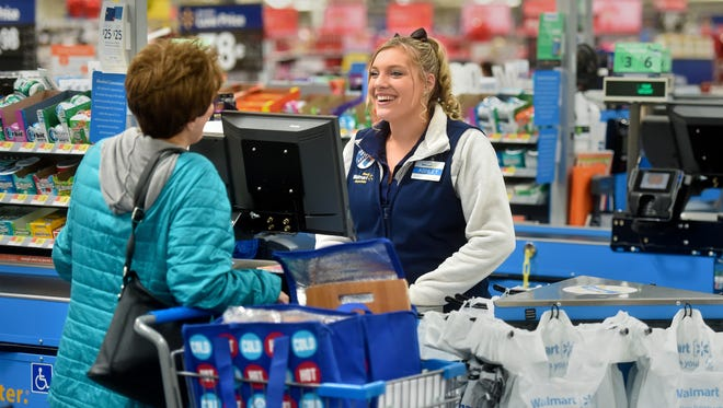 Ashley Zigan, a Wal-Mart cashier, helps a customer at the checkout lane on Wednesday morning.