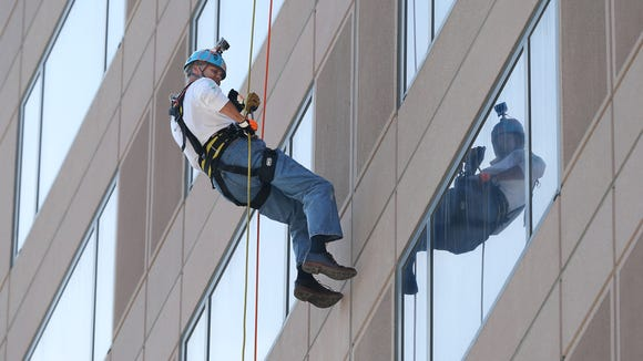 Indiana Sen. Jim Merritt's (R-Indianapolis) rappels down the front of the Westin Indianapolis, 50 South Capitol Ave., on Thursday, September 10, 2015. Merritt, one of about 30 individuals who rappelled down the 15-floor hotel to raise funds for Shatterproof to be used for the prevention, recovery and treatment of addictions, wore a GoPro on his helmet and plans to post video of his adventure on Facebook. Everyone that rappelled had to raise at least $1,000 for Shatterproof, which is conducting 22 such rappelling events across the country this year.
