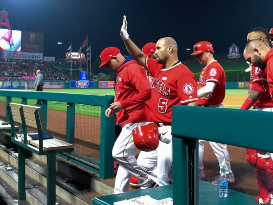 CORRECTS TO GRAND SLAM - Los Angeles Angels' Albert Pujols waves to fans after hitting a grand slam, his 600th homer, as teammates celebrate during the fourth inning of a baseball game against the Minnesota Twins, Saturday, June 3, 2017, in Anaheim, Calif. (AP Photo/Mark J. Terrill)
