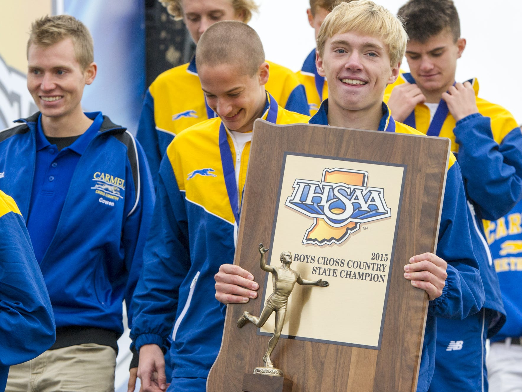 Carmel High School senior Ben Veatch carries the IHSAA state championship trophy off the stage after the awards ceremony at LaVern Gibson Championship Cross Country Course on Oct. 31, 2015, in Terre Haute, Ind. Carmel teams won both the boys and the girls titles.