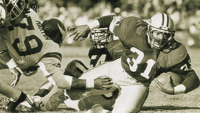 Running back Gerry Ellis tries to evade tacklers during the Green Bay Packers' 26-7 win over the Minnesota Vikings at County Stadium on Nov. 21, 1982. It was the Packers' first game after the 57-day NFL players strike.