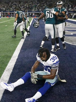 Dallas Cowboys' Brandon Carr (39) sits on the field in dejection as the Eagles celebrate the game-winning touchdown in overtime Sunday night on Jordan Matthews' 41-yard reception.