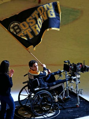 """FILE - In this April 5, 2016 file photo, Actor Jake Gyllenhaal, portraying Boston Marathon bombing survivor Jeff Bauman, waves a flag on the ice of Boston Garden while filming filming a scene for the movie, """"Stronger."""" Hollywood films that portray the bombings have not yet disclosed how much they've sought or received in government subsidies to film in Massachusetts."""