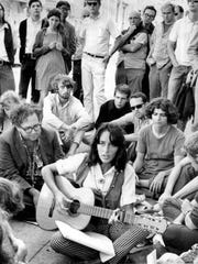 FILE - In this Sept. 22, 1967, file photo, folk singer Joan Baez sits at the corner of Haight and Ashbury in San Francisco, serenading hippies and tourists. City officials have rejected a permit for a planned free concert intended to mark the 50th anniversary of the famed Summer of Love in Golden Gate Park that had been planned for June 2017.