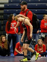 In this Feb. 18, 2017 photo, Euless Trinity's Mack Beggs is consoled by coach Travis Clark after Beggs' opponent forfeited during the finals of the UIL Region 2-6A wrestling tournament at Allen High School in Allen, Texas.  Beggs, who is transgender, is transitioning from female to male, won the girls regional championship.