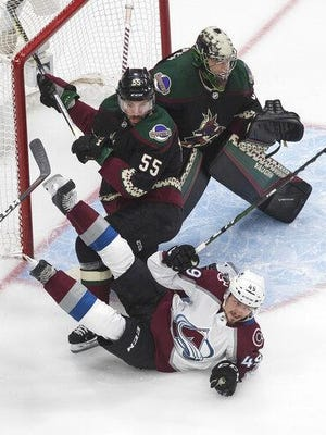 Colorado's Sammel Girard, bottom, is checked by Arizona's Jason Demers, center, as goalie Darcy Kuempe) looks for the shot during the first period in Game 4 of an NHL hockey first-round playoff series in Edmonton, Alberta on Monday.