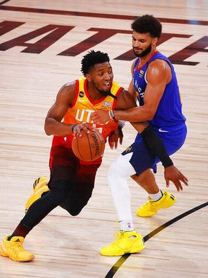 LAKE BUENA VISTA, FLORIDA - AUGUST 08: Donovan Mitchell, let, of the Utah Jazz drives against Denver's Jamal Murray during the third quarter at The Arena at ESPN Wide World Of Sports Complex on Saturday in Lake Buena Vista, Florida. [Getty Images, Kevin C. Cox]]