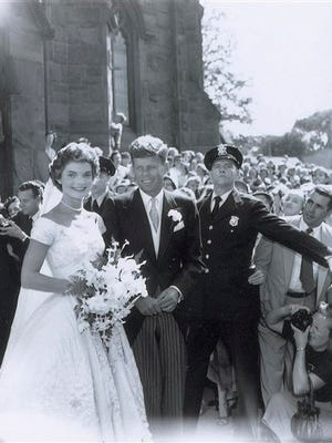 In this Sept. 12, 1953 photo released by RR Auction, John F. Kennedy, Jr., and his new bride Jacqueline leave St. Mary's Roman Catholic Church after their wedding in Newport, R.I. The photo is one of a collection of 13 original images made by Frank Ataman, of Fall River, Mass., being auctioned by RR Auction. The original negatives were discovered in his darkroom after he died. The auction closes Wednesday, Oct. 15, 2014. (AP Photo/RR Auction, Frank Ataman)