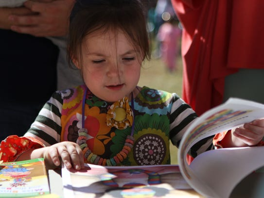"Three-year-old Isabella Brady looks at the book ""A"