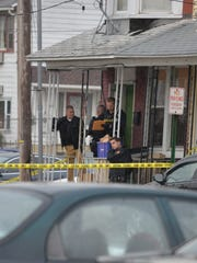 Police officers on the porch of 431 Guilford Street,