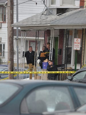 Police officers on the porch of 431 Guilford Street, which was the scene of a shooting Saturday evening, May 21, 2016.