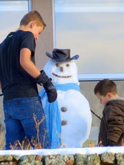 Sunshine melted snow on the ground, but cold temperatures kept this snowman in good shape.