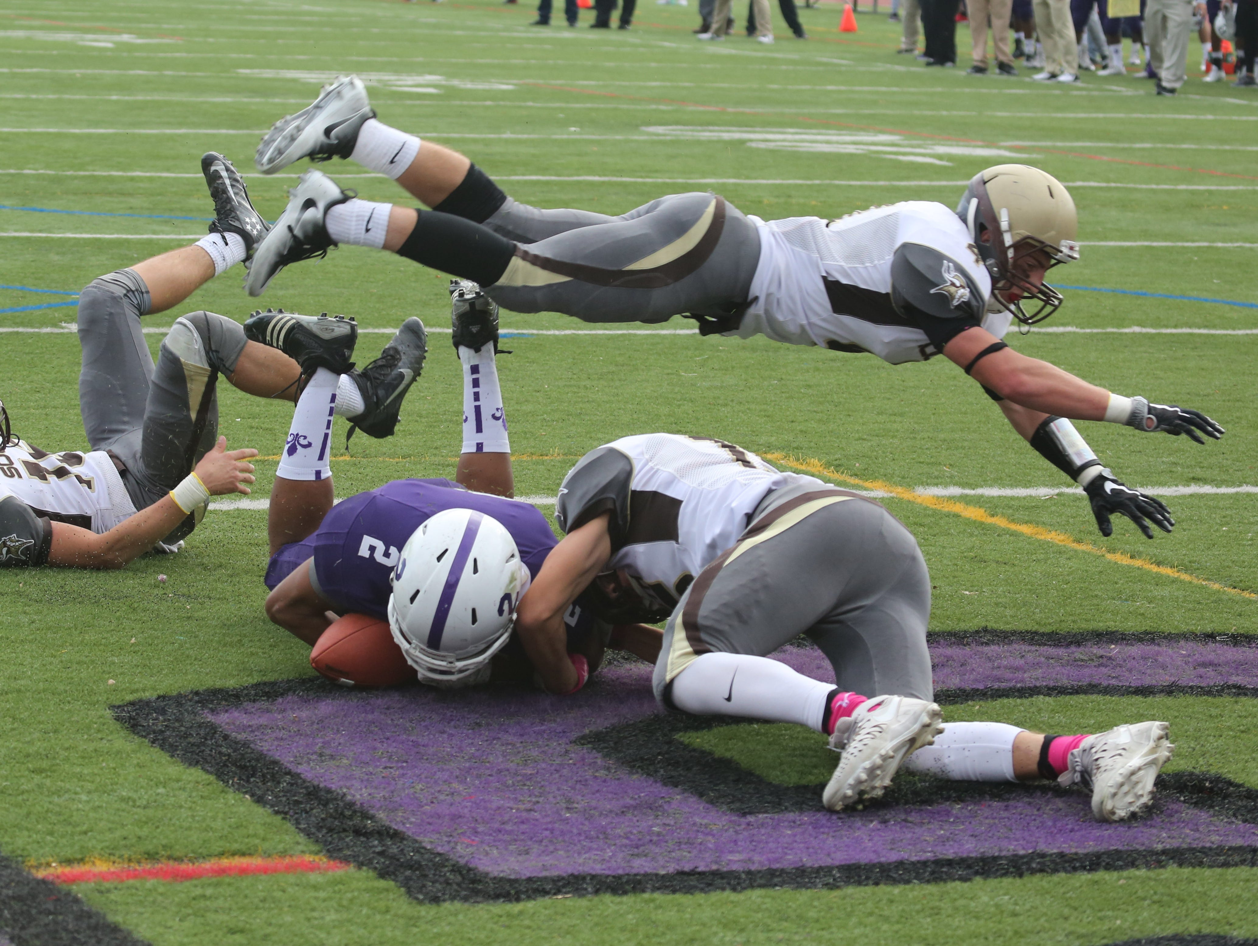 New Rochelle's Romeo Holden's pass is incomplete in the end zone as Clarkstown South players go flying during their Class AA semifinal in New Rochelle Oct. 29, 2016.