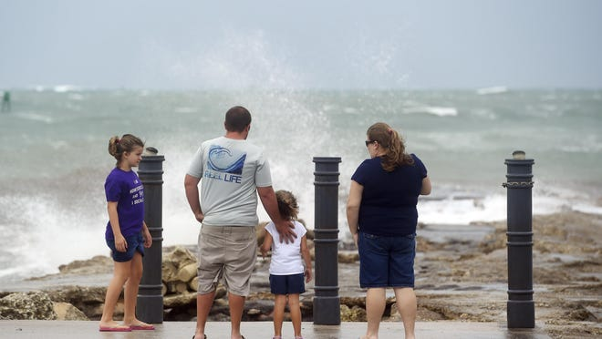 Elizabeth Whittemore (from left), along with her father James, sister Jordan and mother Susan, stand at the end of the South Jetty in Fort Pierce on Sunday, Aug. 2, 2020, watch the waves crash over the rocks brought by the high winds of Tropical Storm Isaias churning off the coast.