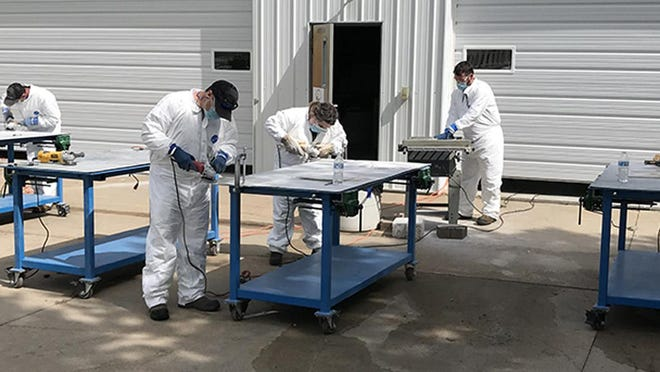 Employees of Suspendem work on blade repairs at the Cloud County Community College Renewable Energy hangar in Concordia.