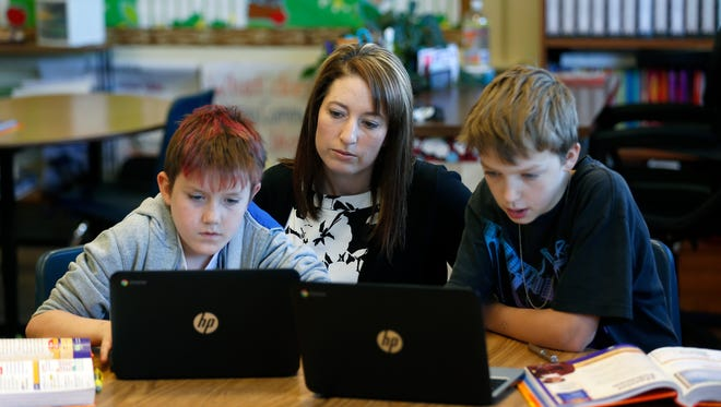York Elementary School teacher Shondra Collins helps students Nathanael Winckler (left), 11, and Nathaniel Haley, 11, as they complete an assignment on Thursday, May 6, 2016.