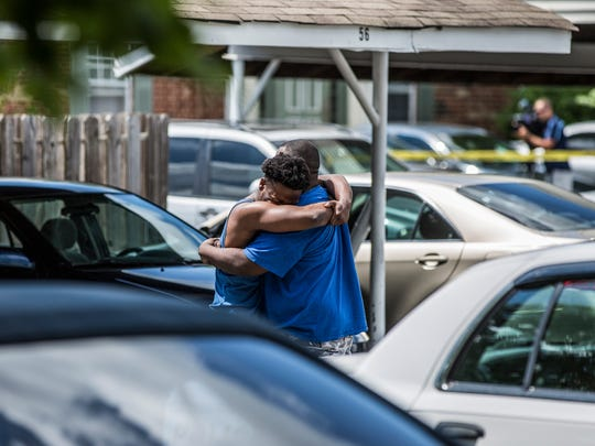 Two men embrace in the parking lot in the 6300 block