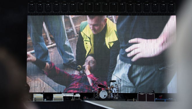 Foo Fighters frontman Dave Grohl addresses the audience in Gothenberg, Sweden from his back after falling onstage.