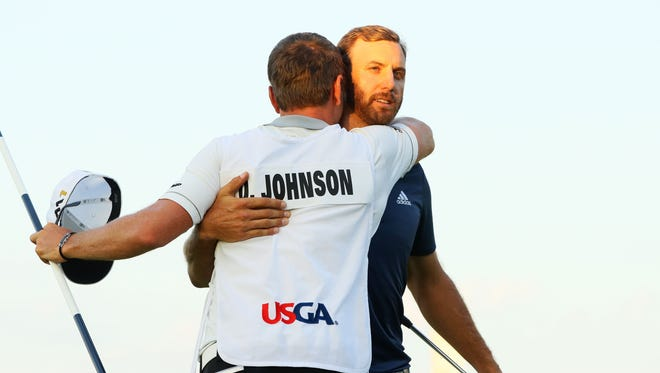 Dustin Johnson of the United States celebrates with caddie Austin Johnson after winning the final round of the U.S. Open at Oakmont Country Club on June 19, 2016 in Oakmont, Pennsylvania.
