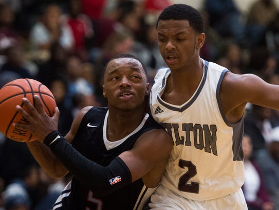 Austin-East's Ronney Pierson (5) takes a shot while defended by Fulton's Trey Davis (2) during a game Saturday.