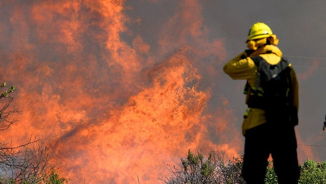 A firefighter from Ventura County Fire Department covers his face Monday from the heat of flames on Canyon Fire burning on Vandenberg Air Force Base.
