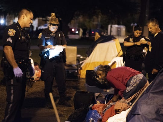 Kalamazoo Department of Public Safety officers issue citations to campers at the Bronson Park encampment in downtown Kalamazoo, Mich., on Wednesday, Sept. 19, 2018.