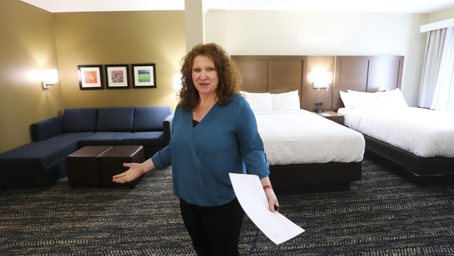 Janell Colburn, regional director of sales for TusCom Properties, shows off a kitchenette room in the newly opened Comfort Inn on Jack Warner Parkway on Thursday.
