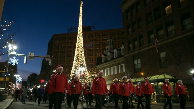 Prime Time Brass leads the parade after the lighting of the Liberty Pole.
