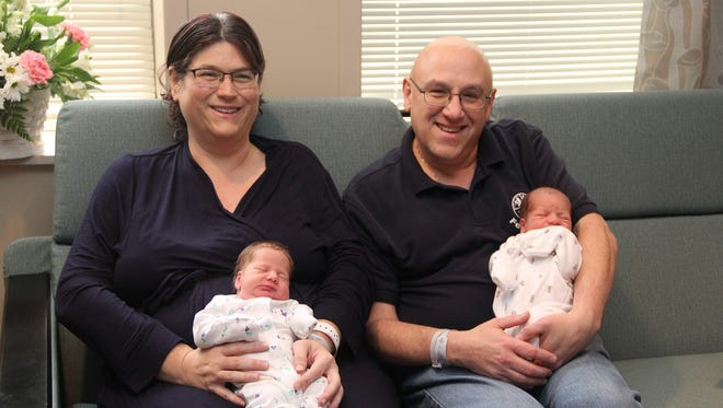 Angela and Gary Summers hold newborn twins Harper and Austin Summers.