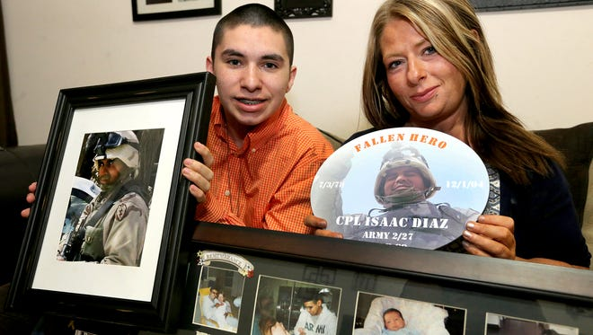 Aaron Diaz, left, and his mother, Amber Diaz, hold photographs of Aaron's father, U.S. Army Cpl. Isaac Diaz, who was killed in active duty on Dec. 1, 2004.