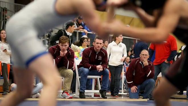 South Kitsap coaches (left to right) Conner Hartmann, Chad Nass and Les Hoyt watch as South Kitsap's Devin Gentz wrestles Olympic's Kaylomb Parrish at the HammerHead Invitational wrestling tournament at the Kitsap Sun Pavilion on Saturday.