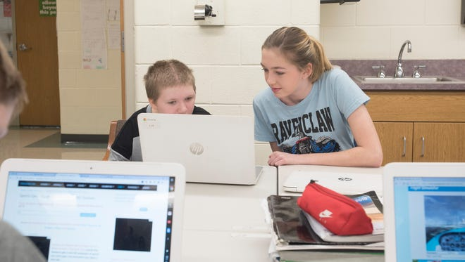 Brooke Hopkins' friend, Kendahl Pollock, helps her in computer class at Huntington Middle School.