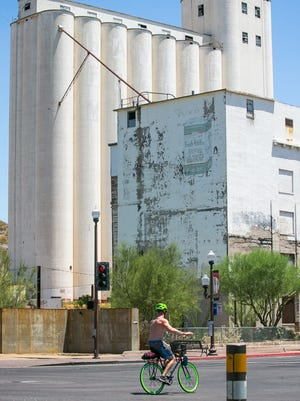 A bicyclist bikes down Mill Avenue past the Hayden Flour Mill in 2014.