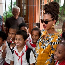 Beyonce poses for photos with school children as she tours Old Havana, Cuba on April 4, 2013.