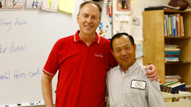 Wausau East High School teacher George Hagge, left, and custodian Chong Lee, pose for a photo Thursday at the high school.