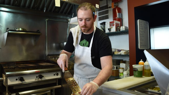 Derric Wetter, owner of Craft Burger in the City of Poughkeepsie, serves three sliders.