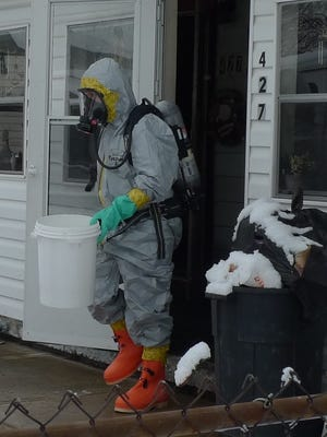 Lt. Chris Adkins of the MARMET Drug Task Force removes material from the house after the raid.
