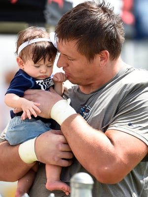 Titans defensive lineman Karl Klug (97) visits with his daughter Cora after practice at St. Thomas Sports Park Tuesday Aug. 11, 2015, in Nashville, Tenn.
