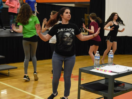 "Powell Middle School choral director Alison Smith walks through a dance scene with members of the cast for ""Singin' in  the Rain""."
