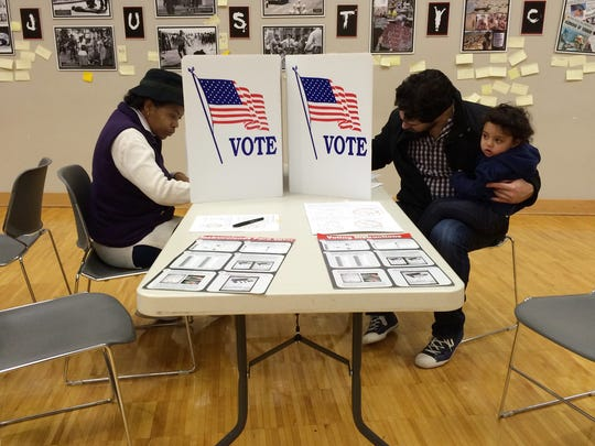 Cynthia Johnson and David Dietrich, with daughter, Jaya, 1, fill out their ballots at School Without Walls on Election Day.