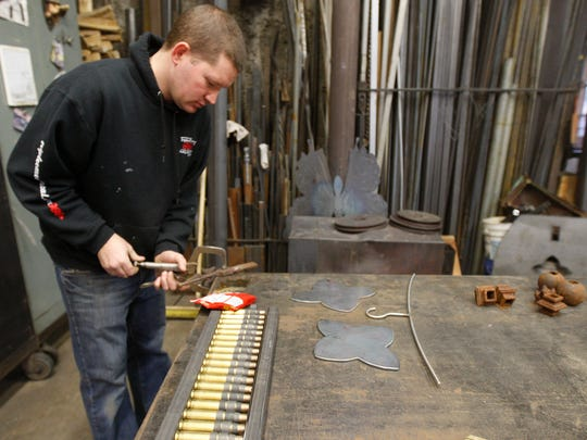 Eric Majewicz works on creating a piece for the flag holder on the memorial for slain Rochester police Officer Daryl Pierson.