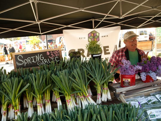 John Whitson talks with customers as they shop at the Grade A Gardens booth Saturday, May 6, 2017 at the Downtown Farmers' Market in Des Moines.