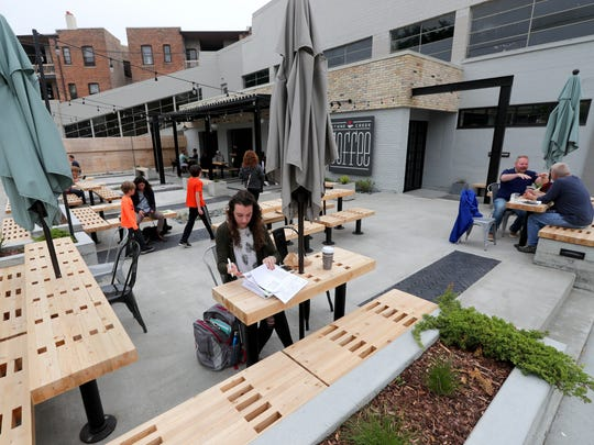 Ariel Powers of Milwaukee studies as she drinks her coffee on the patio at the new Stone Creek Coffee location on Downer Ave.