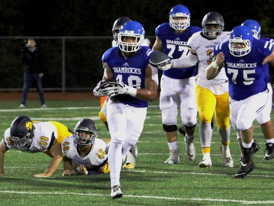 Catholic Central's Matt Young runs for a first down.