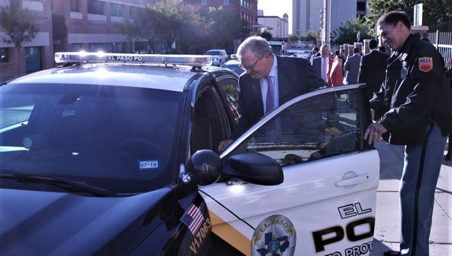 El Paso Mayor Dee Margo gets into a new police car in October across from City Hall as Police Chief Greg Allen watches.