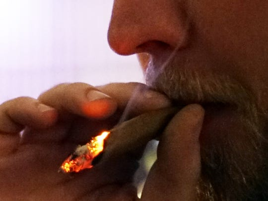 A marijuana user smokes a joint of Colorado-legal cannabis