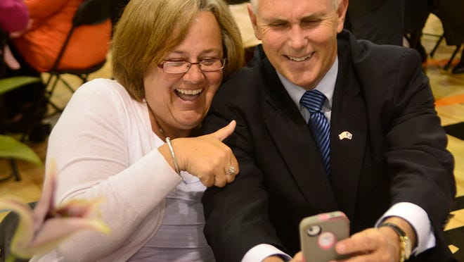 Indiana Gov. Mike Pence poses for a selfie with Cheryl Bartnick at the Primetime Center in Fort Wayne, Ind.