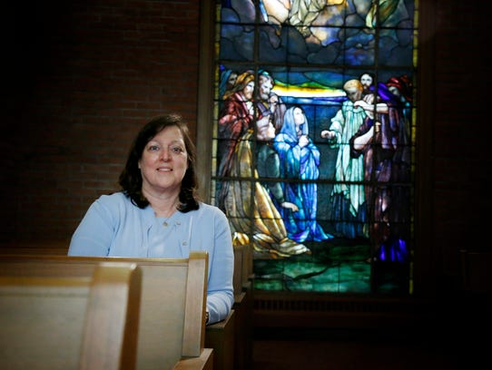 The Rev. Betsey Crimmins sits in front of a Tiffany