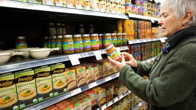 Andrea Stander, an active supporter of the GMO food labeling bill, looks through the labels of processed foods at Hunger Mountain Coop in Montpelier in search of common GMO ingredients like corn and soy.